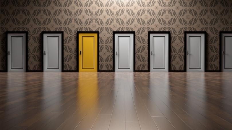 repeating white doors, one bright yellow door